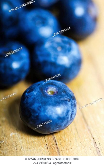 Low depth macro on a blueberry on wooden table surface. Organic superfood