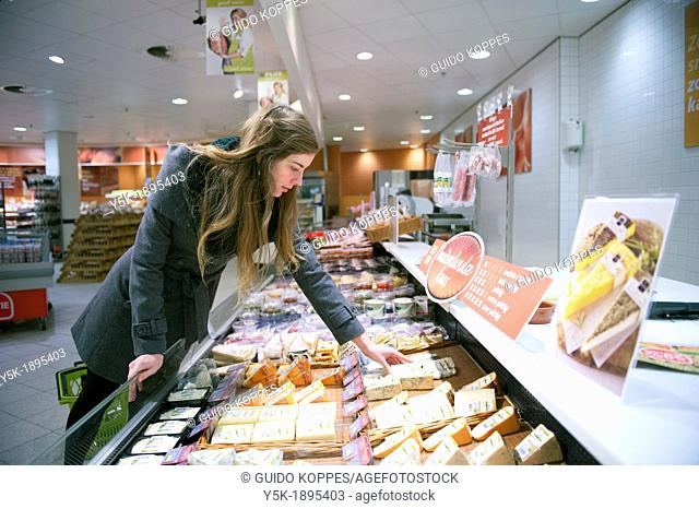 Tilburg, Netherlands. Young woman buying groceries in a supermarket