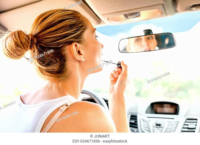 Beautiful young woman in casual summer clothing applying makeup in the car using the rear view mirror to apply red lip gloss as she refreshes her appearance