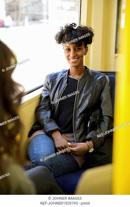 Young woman sitting in train, Stockholm, Sweden