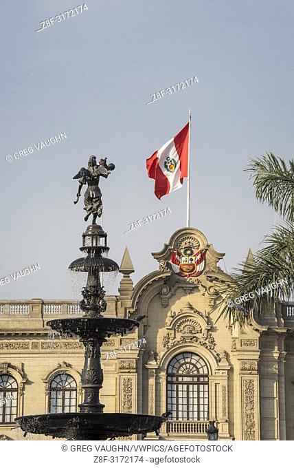 Flag of Peru on Palacio Gobierno (Government Palace) and bronze water fountain in Plaza Mayor; Lima, Peru