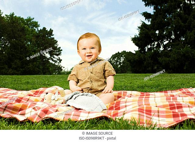 Baby boy on blanket in park