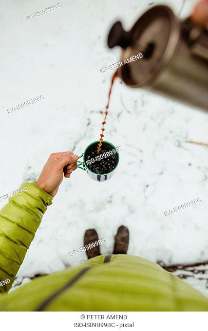 Personal perspective view of male hiker pouring coffee from flask in snow