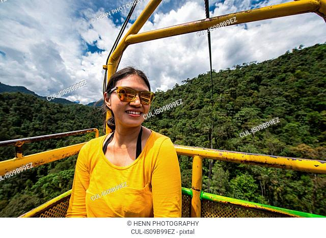 Woman taking a cable car ride at the waterfall in Mindo, Pichincha, Ecuador, South America