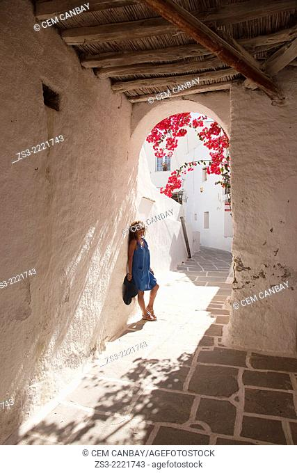 Woman posing at a passageway in town center Chora, Ios, Cyclades Islands, Greek Islands, Greece, Europe