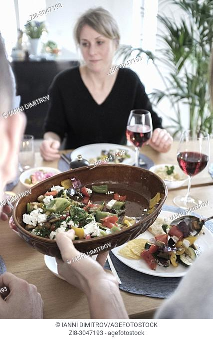 Group of friends casually snacking on a selection of food while laughing and enjoying themselves. Serving roasted vegetables- selective focus