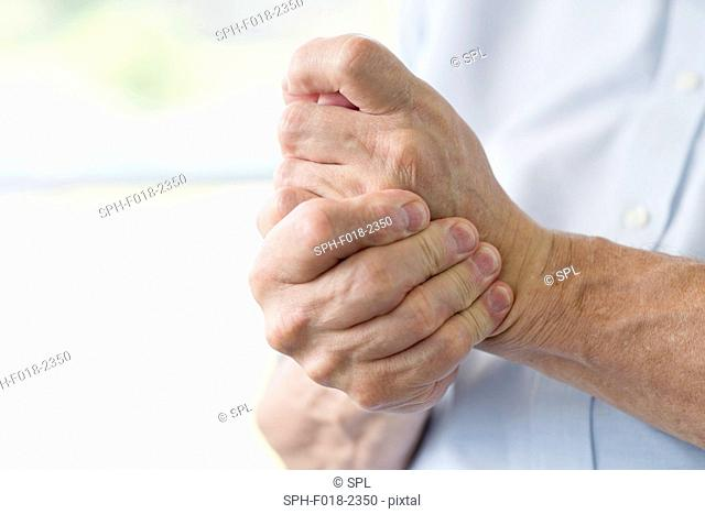 Senior man holding painful hand, close up