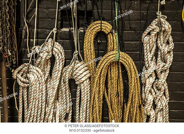 Coils of rope hanging on a brick wall