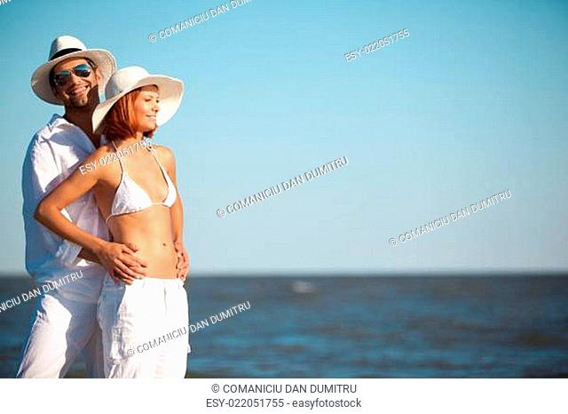 happy young couple standing on the beach