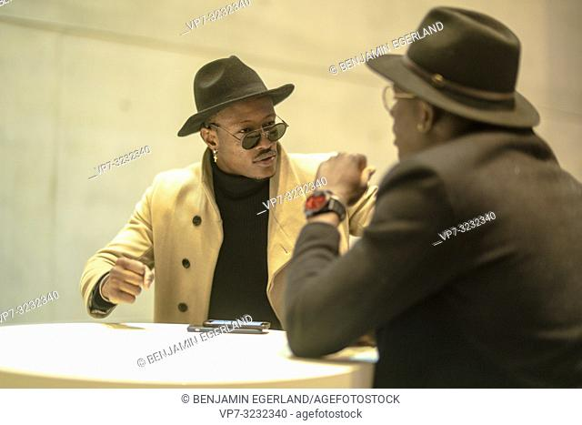 two men, indoors, conversation, sitting at table
