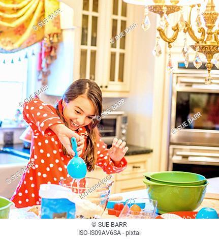 Girl wearing pyjamas at kitchen counter using measuring spoon smiling