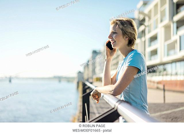 Young woman standing at the riverside, enjoying the sun, talking on the phone