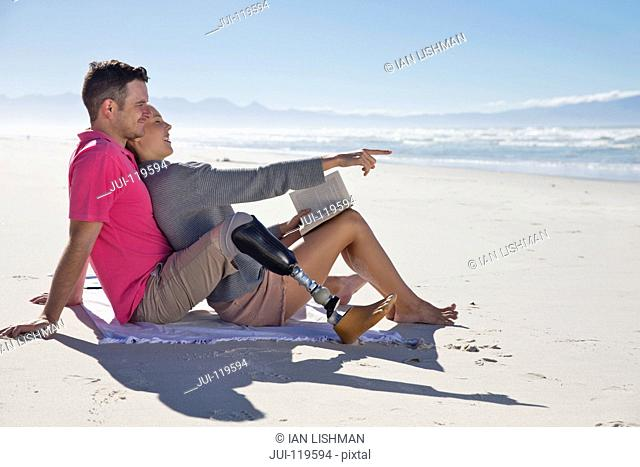 Man With Artificial Leg Sitting And Relaxing With Female Partner On Beach Vacation