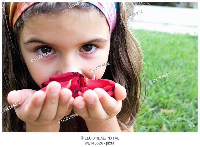 Closeup of a girl looking at the camera holding rose petals in her hands