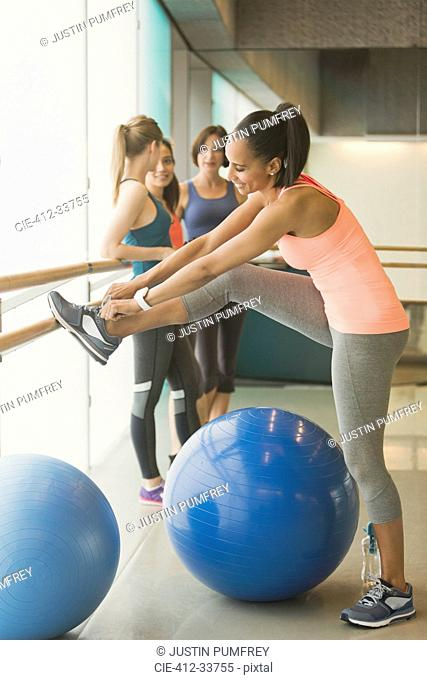 Woman tying shoe at barre in exercise class gym studio