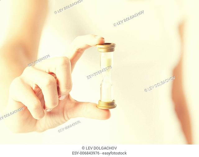 close up of woman hand holding hourglass
