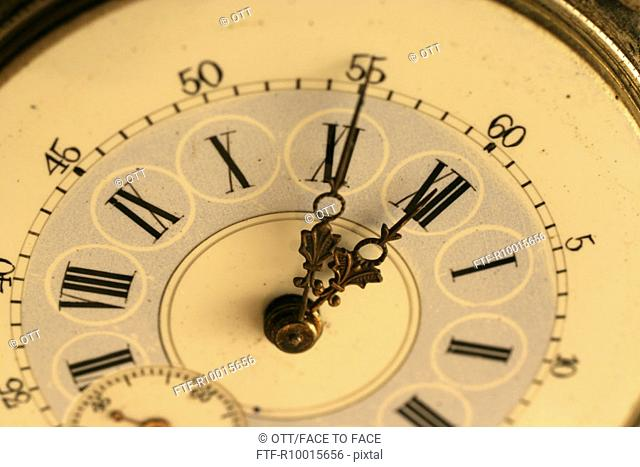 A close up of an antique pocket watch with Roman numbers on the dial