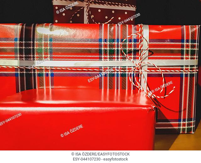 Front view of different size and color decorated gift boxes with ribbons and Christmas decor