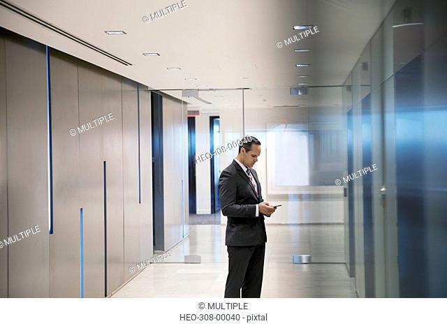 Businessman texting waiting for elevator in office corridor