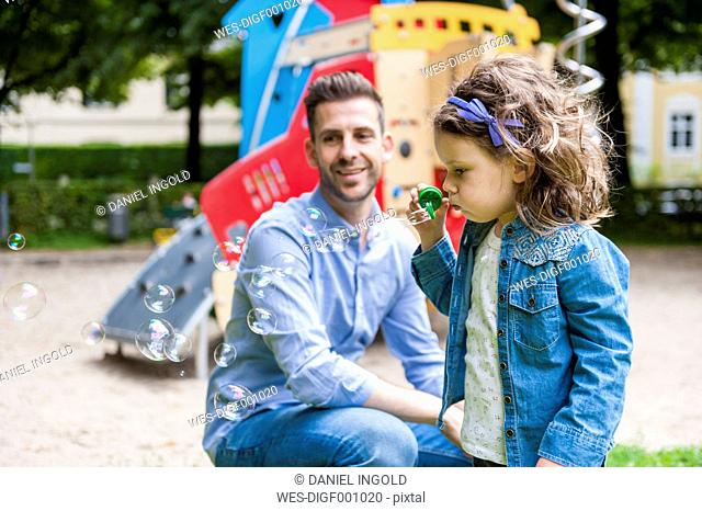 Daughter with father on playground blowing soap bubbles