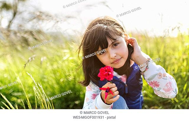 Portrait of little girl with red flower in nature