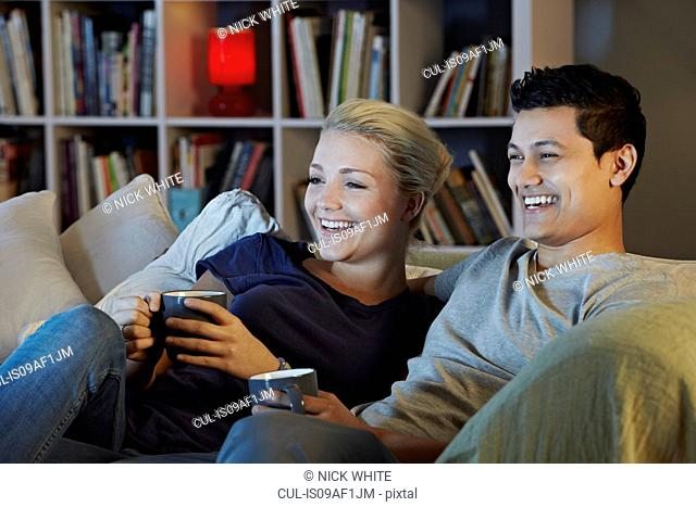 Young couple sitting on sofa with hot drinks, watching tv