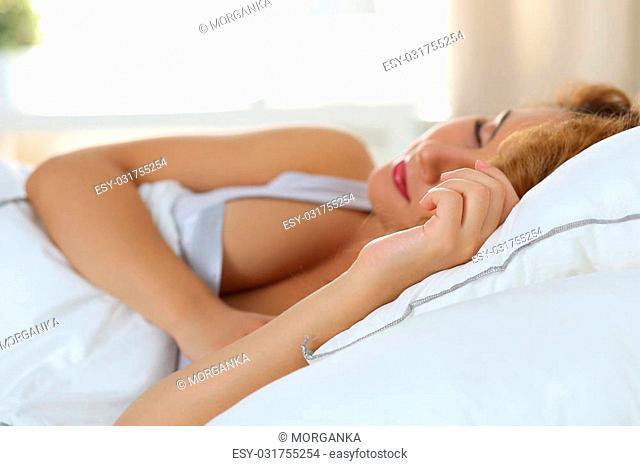 Beautiful woman sleeping in her bedroom in the morning. Focus on hand. Copyspace