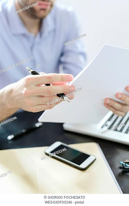 Young businessman working in office, reading documents