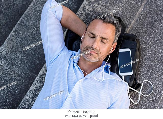 Man with closed eyes lying on stairs with cell phone and earbuds