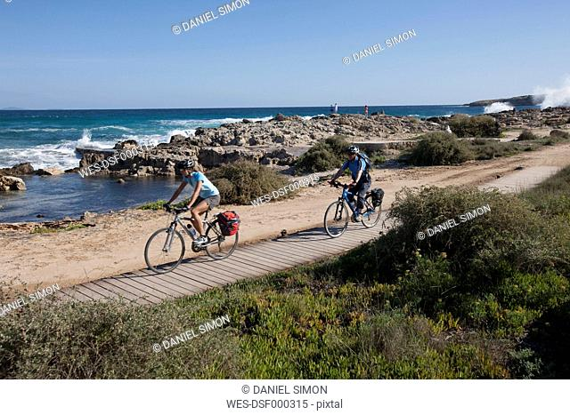 Spain, Formentera, Mature man and mid adult woman riding bicycle