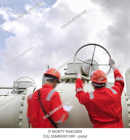 Workers with valve at gas storage plant
