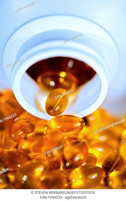 Yellow shiny pills spill out of bottle