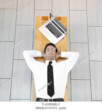 Caucasian businessman sleeping on bench