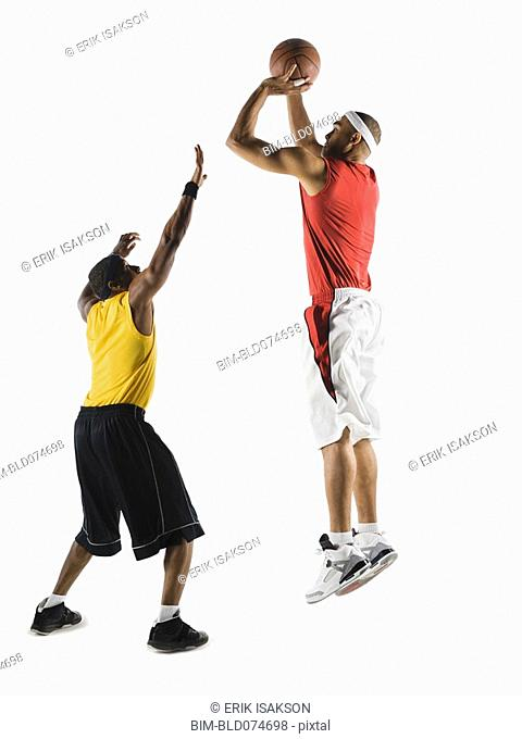 African man shooting basketball over opponent