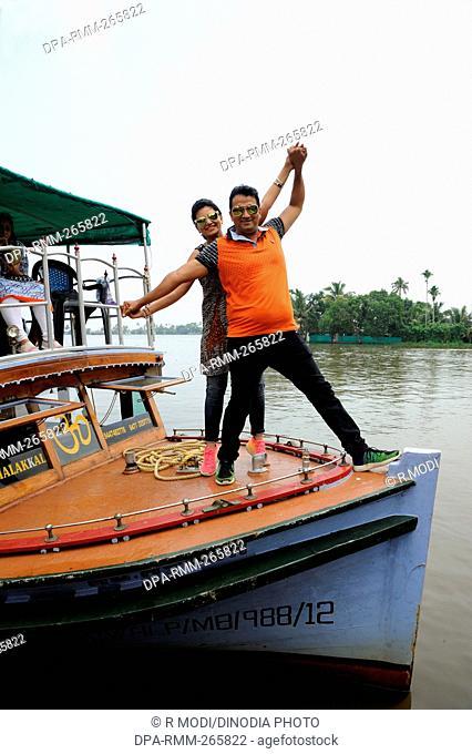 couple posing on deck of boat backwater, Munnar, Kerala, India, Asia, MR#801B, MR#802B