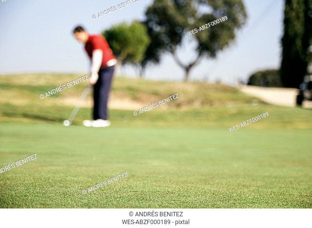 Unfocused golfer playing golf on the green of a golf course