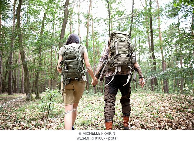 Couple with backpacks on a hiking trip in forest