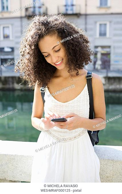 Portrait of smiling young woman text messaging