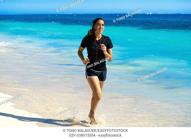 Latin girl running in caribbean shore beach of Mayan Riviera of Mexico