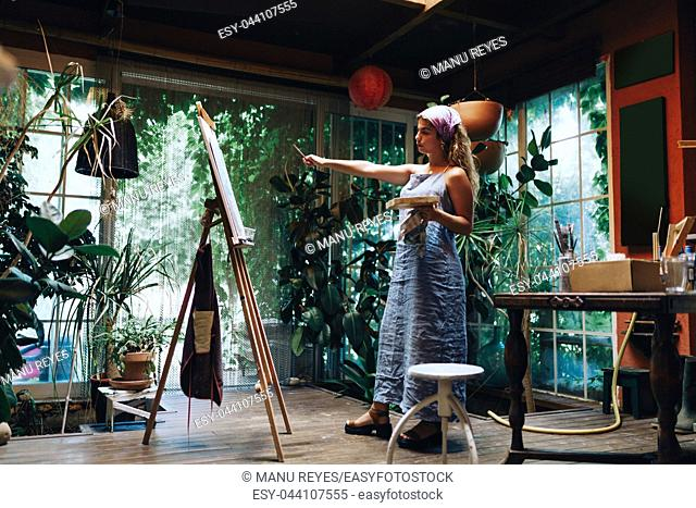 Indoor shot of professional female artist painting on canvas in studio with plants