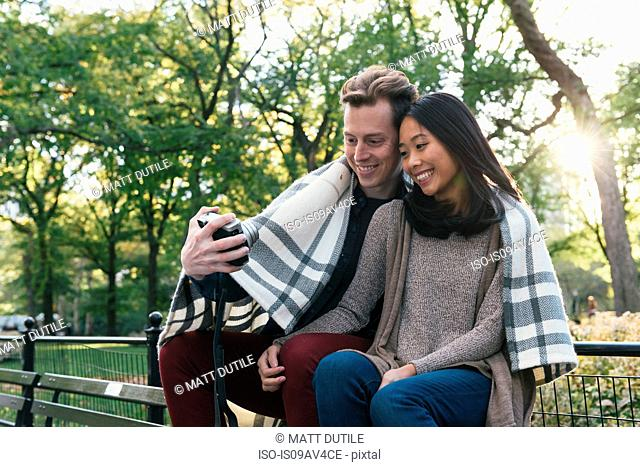 Mid adult couple wrapped in blanket taking instant selfie in park