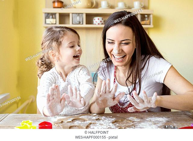 Portrait of laughing mother and her little daughter baking together
