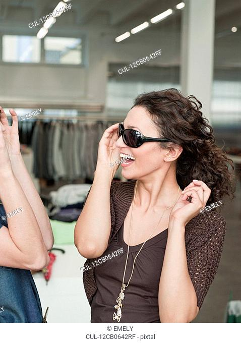 women shopping trying on sunglasses