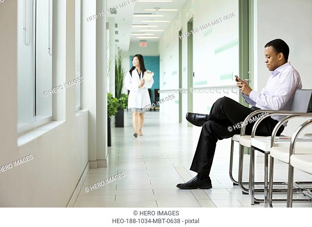 Man using smart phone in waiting area