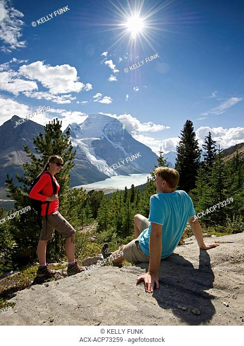 A young couple takes in the morning view of Rearguard Mountain, Mount Robson, Berg lake and the Berg Glacier, just North of Valemount