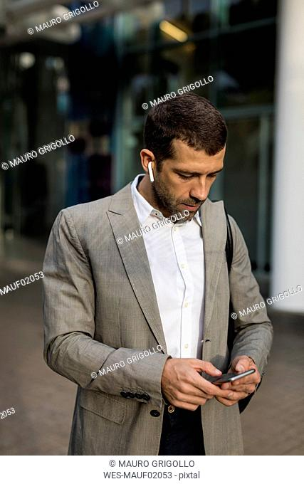 Businessman with cell phone and bluetooth earbuds in the city