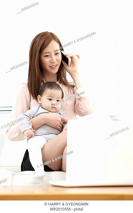 a mother is working while taking care of her baby