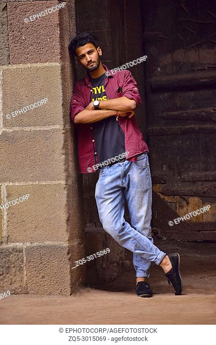 Young man with checked shirt leaning on wall, Pune, Maharashtra