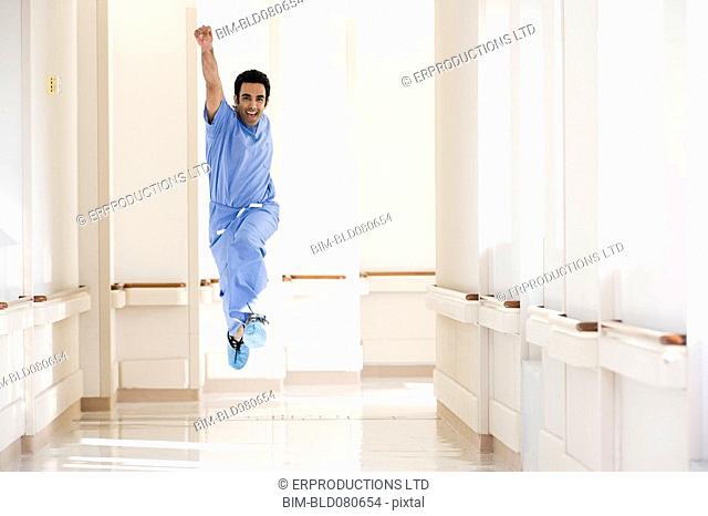 Asian doctor in scrubs jumping in corridor