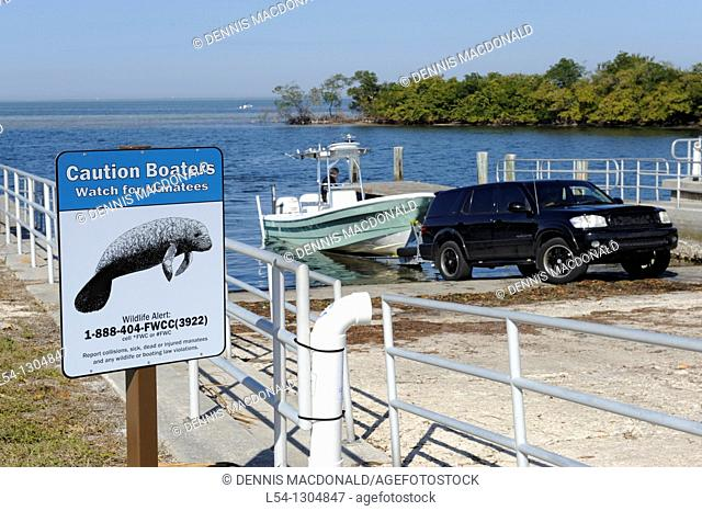 Boat launches into Tampa Bay Florida at Ruskin at Simmons Park with sign caution Manatee area sign as a warning